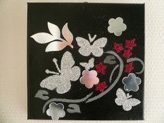 Joli tableau pour décorer un mur : un motif de fleurs et papillon est recouvert de paillettes rouges et argent qui ressortent sur un fond noir. Pour donner encore plus de lumièr - 11757519