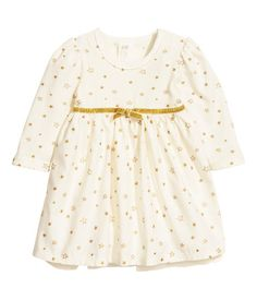 CONSCIOUS. Dress in soft organic cotton fabric with a glittery pattern. Bodysuit in jersey with scalloped trim, long puff sleeves, and snap fasteners on shoulders and at gusset. Attached, flared skirt in woven fabric with tulle lining. Glittery elastication and decorative bow at top of skirt.