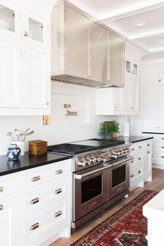 Vintage kitchen runner, black+white counters, and niche behind stove || Studio McGee
