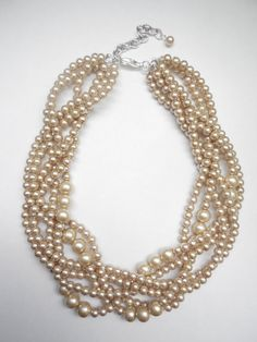 The pricing listed is for 1 - 6 strand Champagne pearl necklace. Prices change per amount of strands. Pearl, braided twisted beaded necklace 18 - 21 inches. Necklace has a lobster claw clasp, and 3 inch extender chain. I can customize it in different colors or sizes of beads and even length of necklace. They are glass pearl beads. Love these necklace so much, wear it with tee and jeans or dress it up. Also great for bridesmaids! I can do a bracelet and earrings to match. Please let me know…
