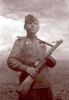 """Soviet orphan, """"son of the regiment"""" packing a PPSh 41 sub machine gun. 1st Bielorussian front, April 1942.The PPSh 41 carryed out a primary role In Russian Army: over 6 million PPSh submachine guns were produced by the end of the war. The Soviets would often equip whole regiments and even entire divisions with the weapon, giving them unmatched short-range firepower. Thousands more were dropped behind enemy lines to equip large partisan formations to disrupt German supply lines and…"""
