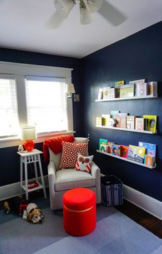 Library Wall in a Baby Boy Nursery - love the navy walls and bright pops of orange!