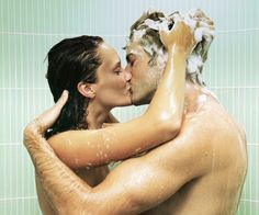 Couple kissing in shower, woman shampooing man's hair