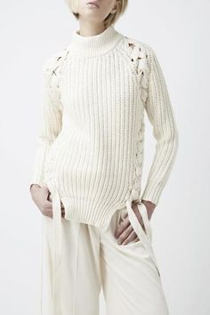 by Finders Keepers ...The Tangled Knit is a pullover jumper with a high ribbed neckband, plaiting detail along the side seams, open sides at the hem band and fitted sleeves in a heavy ribbed knit fabric.