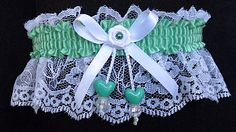 Little Obsessions. SAGE GREEN Garter with a satin band & matching double hearts on white lace. A mini-rose with a sage green pearl eye is in the center of the bow. Garters for Wedding Bridal Prom Fashion. Style # FM-2AN-577 / Visit: www.garters.com/jpage13a.htm