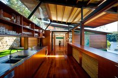 The kitchen is a central hub, its light canopy roof creating the most transparent room in the house. Wide sliding hardwood servery windows open the kitchen to both the pool and the courtyard.
