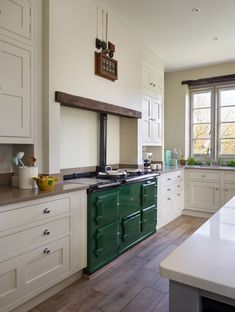 "The neo-classical palette of cream and grey hand painted cupboards is given a pop of colour by the gleaming emerald green Aga. Floor ""American Oak"" wood effect porcelain Martin Moore Stone."