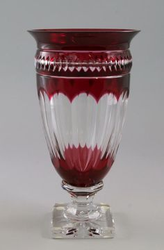 A Val St Lambert ruby and clear flash glass vase, late 20th/ early 21st century, of tapering form, the sides faceted, raised upon square socle base, bearing 'Val St Lambert Cristal Belgium Depose' sticker to side and engraved 'Val St Lambert' to underside, 36cm high. - Price Estimate: £200 - £300