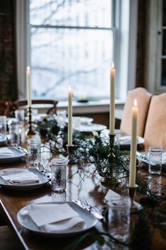 Simple winter place settings with candles and greenery at the dinner table.