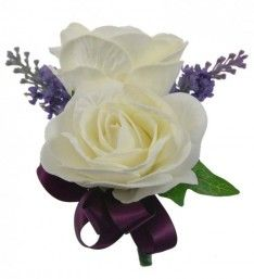 A groom's double buttonhole with two ivory Beth foam roses, with deep lilac silk lavender, finished with a hand tied purple satin ribbon bow and ivy leaf. Purple Satin, Lilac, Lavender, Button Holes Wedding, Foam Roses, Buttonholes, Ribbon Bows, Green Leaves, Ivory