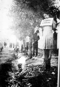 Russia, Jews hanged from trees, wearing signs listing their crimes.