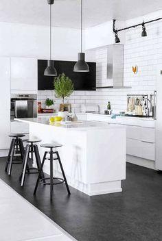 Czarna posadzka , stołki i lampy w białej kuchni skandynawskiej