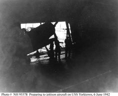 "Battle of Midway, June 1942  Scene in the hangar of USS Yorktown (CV-5) during salvage operations on 6 June 1942. A Douglas TBD-1 ""Devastator"" torpedo plane is being prepared for jettisoning, as part of efforts to lighten the listing ship. Photographed by Photographer 2nd Class William G. Roy. This view looks to port, out the forward hangar bay opening, with the sea visible beyond."