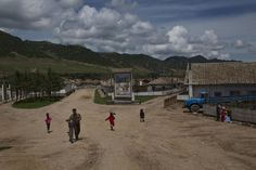 In this June 19, 2014 photo, residents of a small roadside town walk towards the main road in North Korea's North Hamgyong. (AP Photo/David Guttenfelder)