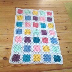 Liten färglad filt i mormorsrutor. En mjuk virkad filt i glada färger, mörkrosa, ljusrosa, mintgrön, lila, turkos, blå och gul. Passar som babyfilt eller som dekoration i trädgårdsgruppen.