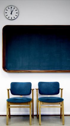 Indigo upholstered chairs and modern chalkboard with gilded frame.