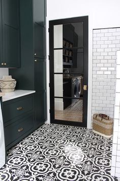 A modern classic black and white laundry room layered with gorgeous dark green cabinets and natural white oak wood accents. Laundry Room Tile, White Laundry Rooms, Modern Laundry Rooms, Laundry Room Cabinets, Laundry Room Storage, Laundry Room Design, Colorful Laundry Rooms, Landry Room, Black And White Tiles