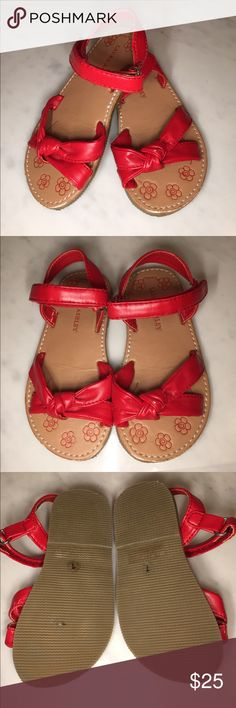 New Laura Ashley sandals in red These are adorable with knots on the front and velcro straps to go around the ankle. They are made of leather and the is a small white mark on top of the knot on the left shoe. Shoes Sandals & Flip Flops