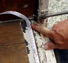 He's measuring the width.  彼は幅を測定している。