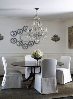 Love the chandelier, white slip-covered chairs and dark round table    Tracery Interiors