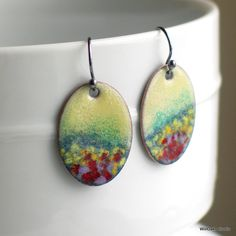 A field of summer flowers rendered in copper enamel in many colors on miniature disks for original handmade artisan earrings. Vitreous enamel,