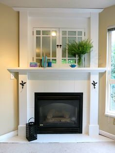 Faux mercury glass old cabinet doors, white tile fireplace surround, vintage entertainment unit, crown molding mantle, mirror above mantlepiece, krylon looking glass spray paint, mullioned window panes, distressed look, decorative iron hooks, built-in storage, aged window cupboard, corner angle gas fire
