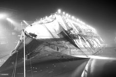 The S.S. Normandie a French ocean liner, lies on its side. The ship eventually caught fire and sunk at teh New York passenger ship terminal.