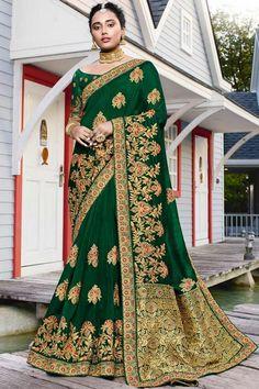Dark Green satin silk saree with dark green art silk blouse. Saree embellished with resham work, stone and zari work. Saree with Boat Neck, Half Sleeve. It comes with unstitch blouse, it can be stitched to 32 to 58 sizes. #weddingsaree #weddingwearsaree #festivalwear #partywearsaree