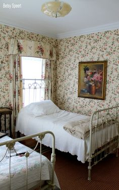 Wallpapered bedroom adds to the beauty of these old iron beds