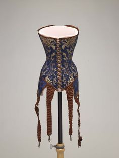 Front laced corset with long satin garters, blue cotton with brown embroidery, ca. 1905–1908.