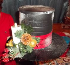 Centerpiece I  made for my daughters Teacher from a Coffee can, a record, a toilet paper tube, a tea light, some floral picks , a piece of ribbon, black paint and spray snow. I filled the inside with Christmas cookies.
