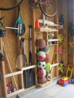 Garage organization using space between shelves to hold sports equipment & toys.  Use bungees to wrangle balls.