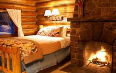 Love this sweet rustic cabin bedroom! Perfect spot with the fireplace.