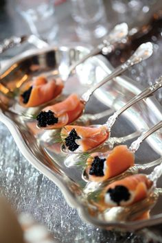 Smoked Salmon resting on silver spoons filled with sour cream, black caviar, and dill