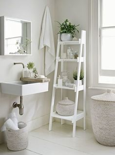Make your ensuite feel more spacious by painting the floors and walls in a warm white and choosing white accessories. A wall-hung basin keeps the floor area free, and a slim tapering ladder shelf unit provides essential storage. Potted plants and bud vases filled with greenery break the all-white scheme and add a natural touch. Get the look: Bathroom ladder shelf, £295, The White Company