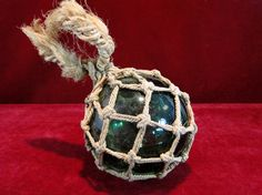 93) Vintage green glass fishing float with original rope net Est. £5-£10