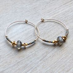 These Labradorite, Gold and Grey 30mm Hoops were created by hand in London.The earrings are a noticable size at 30mm in diameter and are adorned in a very bohemian yet elegantly edgy way, using fair trade, faceted, 22 carat gold vermeil beads along with assymetrically cut labradorite gem stones and grey glass beads. They can be worn day and night and look fab with floating layers as well as structured monocrome beige/white. They would make a great gift for any woman who likes to...