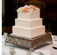 To showcase their intricate cake stand, Susie and Jason opted for a simple square buttercream cake topped with fresh flowers.