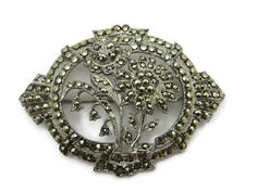 A lovely vintage Art Deco sterling silver and marcasite flower brooch. Some of the flowers are lily of the valley. It is incredibly detailed.