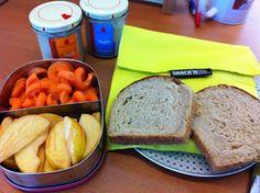 Zusammenstellng von Petzis Mittwochsfrühstück: Brot, zweierlei Rapunzelaufstrich, dazu Karottenspiralen und Apfelspalten