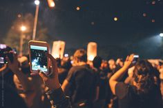 Festival time - People taking photos on phone of fire lanterns flying in the night sky by JovoJVNVC   Stocksy United