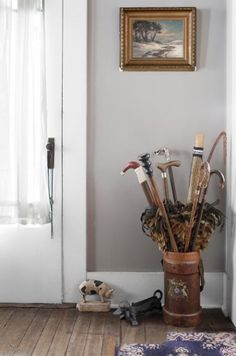 Proesel's collection of walking sticks and feather dusters finds a home in an English-leather fire bucket from the late 1800s. The midcentury pig doorstop and dachshund boot scraper are both made of cast iron.