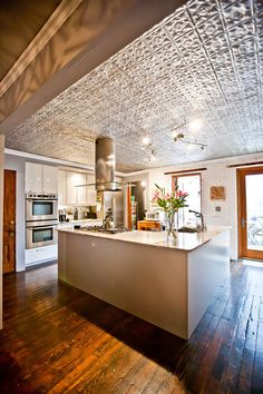 Vintage tin tile used along with repurposed salvage floor beams connects the modern kitchen style to the brownstone renovation...
