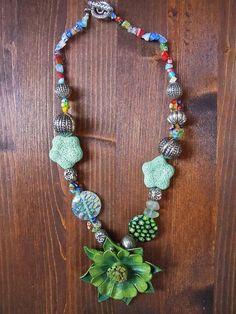 New entry..collana colorata con vetrini millefiori colorati, metallo, frammenti di vetrini e fiore di cuoio nei toni del verde.
