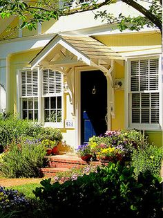 Deep blue front door with yellow walls, white trim. Cottage with style.