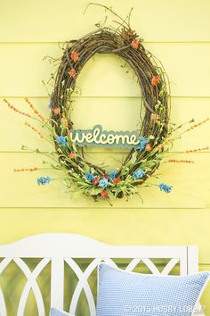 If a wreath is a facelift for the front door, this porch-side pretty is a full makeover! We used sprays of wildflowers in an oval grapevine wreath for a minimalist-chic look and added a hand-painted chipboard sign for extra cheer.