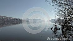 Capture of a serene lakescape framed with bare branches. The photo was taken in Kastoria, Greece.