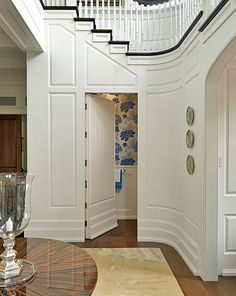 Hidden powder room under the stairs.    Catalano Architects - Architecture and Interior Design -  Boston Design Guide.  Huge fan of the hidden door...