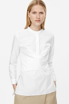 Made from pure cotton poplin, this shirt has a wrapped front drape and long back hem. Coming in at the waist, it's completed with a grandad collar and long cuffed sleeves.