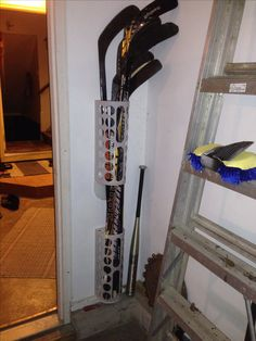 Hockey stick organizer with IKEA plastic bag holders.